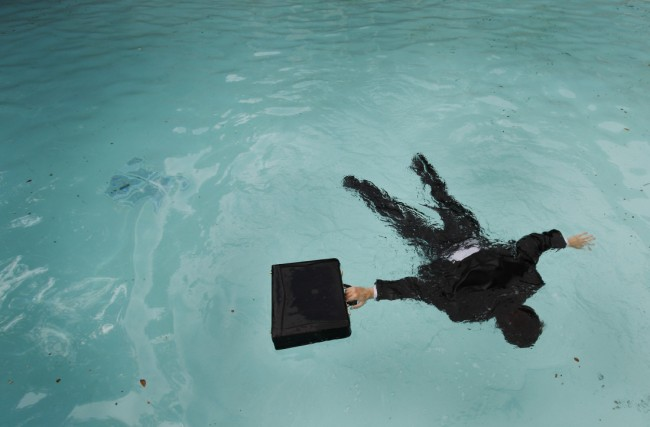 Business man with briefcase floating face down in pool